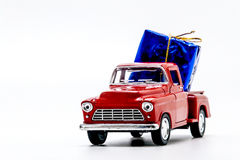 Red retro car pickup with a blue gift box isolated Royalty Free Stock Photos
