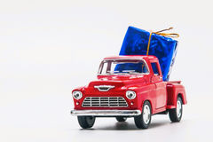 Red retro car pickup with a blue gift box isolated Royalty Free Stock Photography