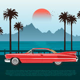 Red retro car on road near blue sea or ocean with palm trees and mountains Royalty Free Stock Photo
