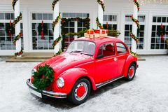 Red retro car standing in backyard. Volkswagen beetle. New year presents royalty free stock images