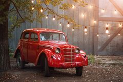 Red retro car standing in the garden in the summer on a background of gray wall and burning bulbs. Vintage vehicle near the garage Stock Image