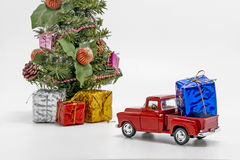 Red retro car toy carries a box with a gift for Christmas tree Stock Image