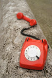 Red retro phone. Red dial phone on stone wall Royalty Free Stock Photos