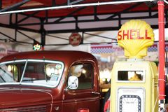 A red retro pick-up truck nearby the SHELL gas station stock photography
