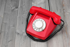 Red retro rotary phone on a wooden platform. Stock Photography
