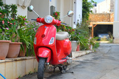 Red retro scooter on street in old part of Malia. Stock Image