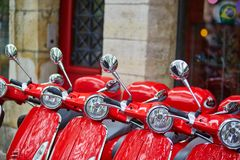 Red retro scooters parked on a Parisian street. Row of red retro scooters parked on a Parisian street Royalty Free Stock Photography
