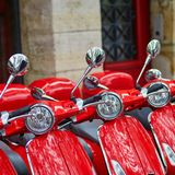 Red retro scooters parked on a Parisian street Royalty Free Stock Photos