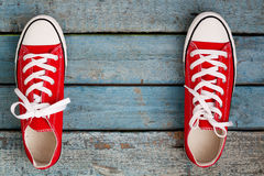 Red retro sneakers on a blue wooden background Royalty Free Stock Photography
