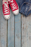 Red retro sneakers and jeans on a blue wooden background Royalty Free Stock Photos