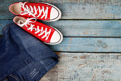 Red retro sneakers and jeans on a blue wooden background Royalty Free Stock Photo