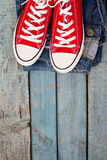 Red retro sneakers and jeans on a blue wooden background Stock Images