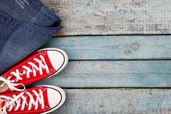 Red retro sneakers and jeans on a blue wooden background Stock Photos