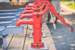 Red retro style hand water pump Royalty Free Stock Image