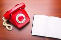 Red retro telephone with notebook Stock Images