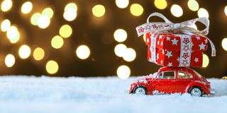 Red retro toy car delivering Christmas or New Year gifts. On festive background stock photo