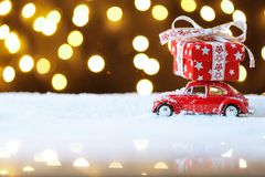 Red retro toy car delivering Christmas or New Year gifts. On festive background royalty free stock photos