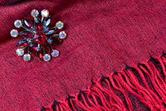 Red rhinestone brooch on a red scarf with fringe, background. Horizontal aspect Stock Photos
