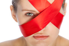 Red ribbon. Covers face of a young woman Stock Photo