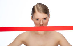 Red ribbon. Covers face of a young woman Royalty Free Stock Photography