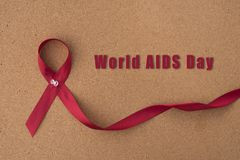 Red ribbon aids ribbon on notice board with `World Aids Day` word. stock photo