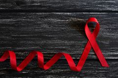 Red ribbon awareness on black wooden table background for World Aids day campaign. Closeup red ribbon awareness on black wooden table background for World Aids stock photos