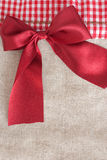 Red ribbon. On beige fabric background Stock Image