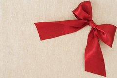 Red ribbon. On beige fabric background Royalty Free Stock Photos
