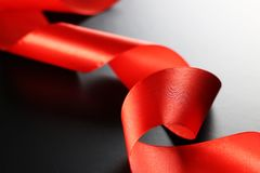 Red ribbon on black. Background with light Stock Images