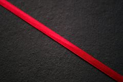 Red ribbon on black, texture. Close up photo of a bloody red textile ribbon that shares black shale surface in two similar parts through diagonals. Good Stock Image