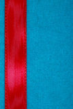 Red ribbon on blue fabric background with copy space. Royalty Free Stock Image