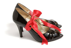 Red ribbon bow and black shoes Royalty Free Stock Photo