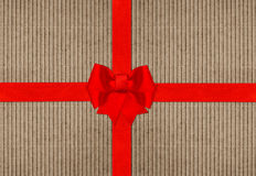 Red ribbon bow on cardboard paper texture Stock Photo