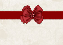 Red Ribbon Bow on a Cream Background Royalty Free Stock Photo