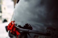Red ribbon bow on the door handle of a black car stock photography