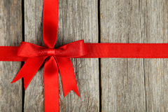 Red ribbon with bow on grey wooden background. stock photo