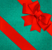 Red ribbon bow over blue recycled cardboard Stock Images