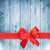 Red ribbon with bow over christmas snow wood background Stock Photos