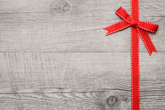 Red ribbon and bow over wooden background Royalty Free Stock Photos