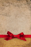Red ribbon bow on textured paper background Royalty Free Stock Images