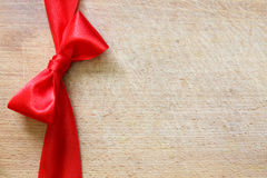 Red ribbon and bow on vintage cutting board christmas background. Concept Royalty Free Stock Images