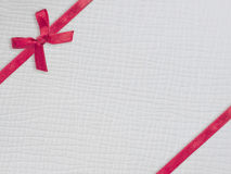 Red ribbon and bow on white leather Stock Photo