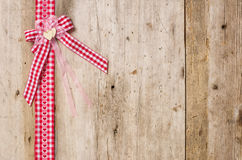 Red ribbon with bow on a wooden background Stock Image