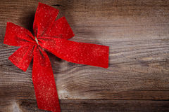 Red ribbon bow on wooden board Royalty Free Stock Images