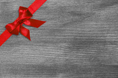 Red ribbon bow on wooden surface Royalty Free Stock Photo