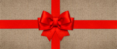 Red ribbon bow on wrapping paper texture. Holidays background Royalty Free Stock Photo