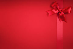 A red ribbon bows. On red background Royalty Free Stock Photo