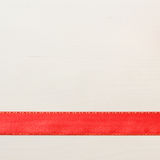 Red ribbon on bright wooden surface with copy space. Royalty Free Stock Images