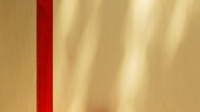 Red ribbon on bright wooden surface with copy space. Royalty Free Stock Photo