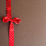 Red ribbon on brown Royalty Free Stock Images